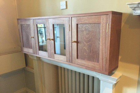 A bespoke hardwood box to hide fire alarm control box in a school in Hampshire